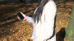 Slowmotion young woman stands in park, holds mobile which slips out and drops  Stock Footage
