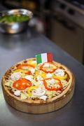 Pizza with italian flag in a commercial kitchen Stock Photos