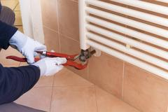 Plumber performs a repair of a radiator - stock photo