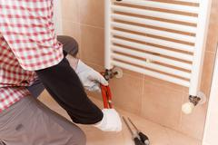 Plumber performs a repair of a radiator - stock photo
