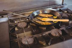 Fish frying in a pan in a commercial kitchen Stock Photos