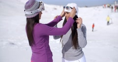 Two stylish young woman chatting at a ski resort Stock Footage