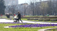 Mother with stroller walking in a park in Sofia Bulgaria Stock Footage