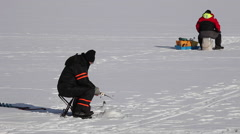 Ice fishing, fishermen sitting Stock Footage