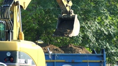 Slowmotion bucket dumps a soil to goods trailer Stock Footage