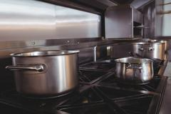 Pots and pans on stove top in commercial kitchen Stock Photos