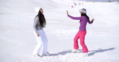 Two young woman frolicking in winter snow Stock Footage