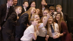 4K Teacher & students pose for a selfie in school theatre Stock Footage
