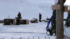 People get dogs ready for a sled run in Longyearbyen, Norway. - stock footage