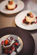 Plates of dessert at the order station in commercial kitchen Stock Photos