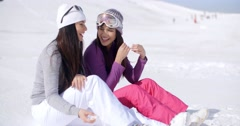Two Friends Sitting Together on Sunny Ski Hill Stock Footage