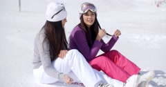 Two young women friends relaxing in the snow Stock Footage