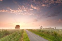 beautiful sunrise on Dutch farmland with windmill - stock photo