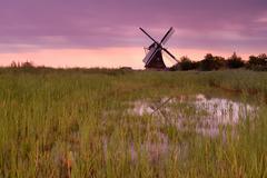 Dutch windmill at purple sunrise Stock Photos