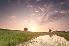 Beautiful windmill at summer sunrise Stock Photos