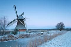 charming windmill in winter at sunrise - stock photo