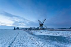 windmill by frozen river in winter - stock photo