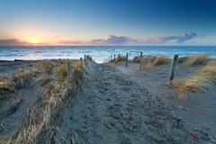 Sand path to North sea beach at sunset Stock Photos