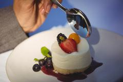 Woman tucking into cheesecake dessert at the restaurant Stock Photos