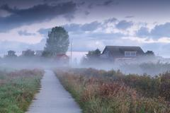Dutch farmhouse in dense morning fog Stock Photos