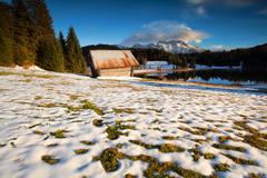 Old wooden hut on snow alpine meadow Stock Photos