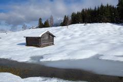 wooden hut on snow meadow - stock photo