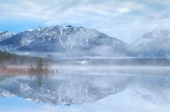 Beautiful misty morning on lake in Alps Stock Photos