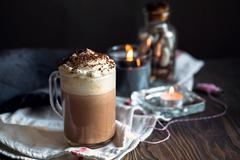Mug of hot chocolate or coffee with whipped cream on the top. - stock photo