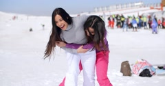 Two playful woman frolicking in the snow Stock Footage