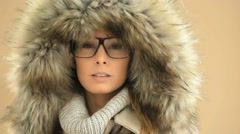 Woman with eyeglasses wearing fur hood, isolated Stock Footage