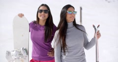 Two attractive young women with their snowboards Stock Footage