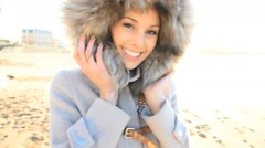Cheerful attractive woman with winter coat and fur hood - stock footage