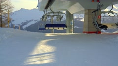 Stock Video Footage of Ski chair-lift with skiers in snow-capped mountains at Alps
