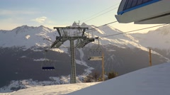 Ski chair-lift with skiers in snow-capped mountains at Alps - stock footage