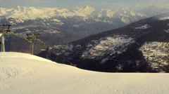 Ski chair-lift with skiers in snow-capped mountains at Alps Stock Footage