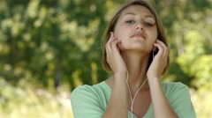 Young woman listening to music through headphones Stock Footage
