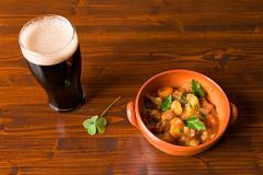 Traditional Irish Stew with a pint of stout beer and a shamrock Stock Photos