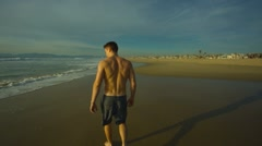 Man walking down beach during sunset Stock Footage