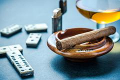 Cuban cigar in ashtray and domino game Stock Photos