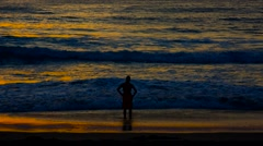 Man silhouetted at beach sunset Stock Footage
