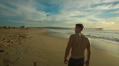 Man walking down beach towards boardwalk - stock footage