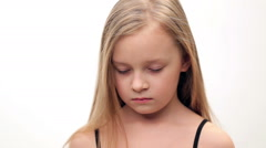 Little girl with blond hair shows sadness, sorrow. - stock footage