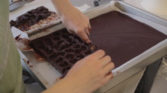 Chocolate mousse truffles cored out of a chocolate mold and smoothed by hand Stock Footage