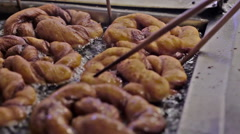 Cinnamon rolls in a fryer being turned by chopsticks Stock Footage