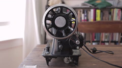 Old electronic sewing machine seen from the side in slow track from bookshelf - stock footage