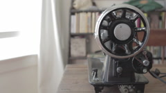 Old electronic sewing machine seen from the side in slow track from window Stock Footage