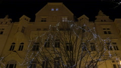 View of a leafless tree with Christmas lights seen at night in Prague Stock Footage