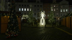 Angel decoration seen at night between Christmas trees in Prague Stock Footage