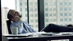 Happy businessman talking on cellphone, sitting by the window in the office - stock footage