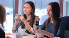 Three smiling girlfriends drink coffee and communicate Stock Footage